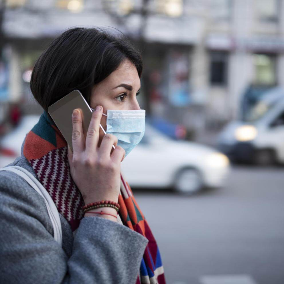 Young Woman With Face Mask Talking On The Phone. stock photo