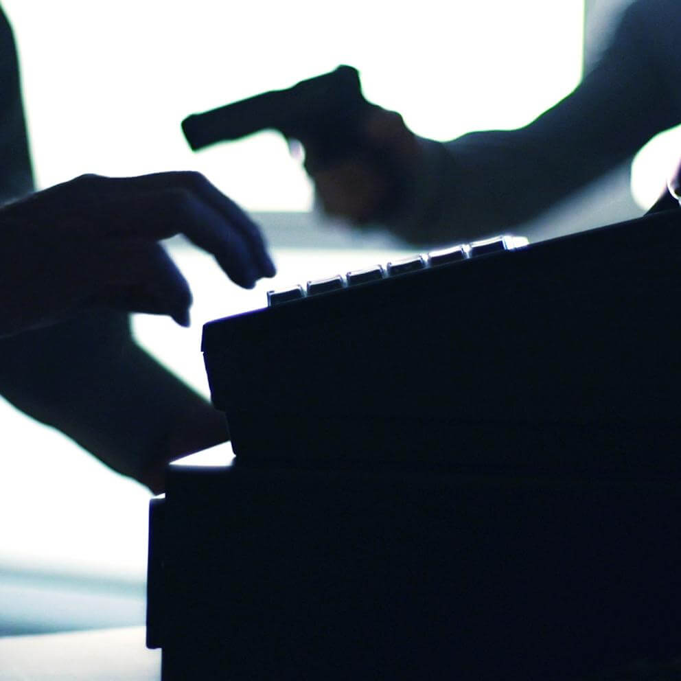 silhouette of cash register and armed robber