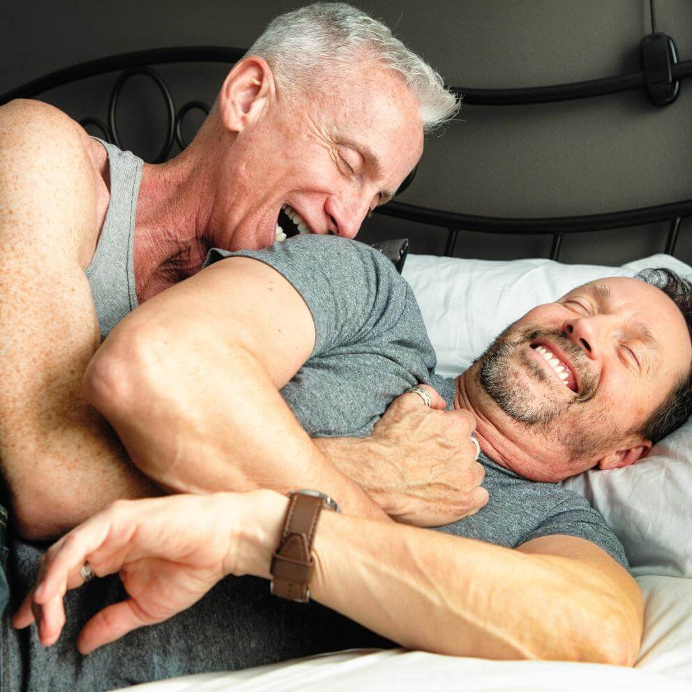 stock photo of an older gay male couple snuggling playfully in a bed.