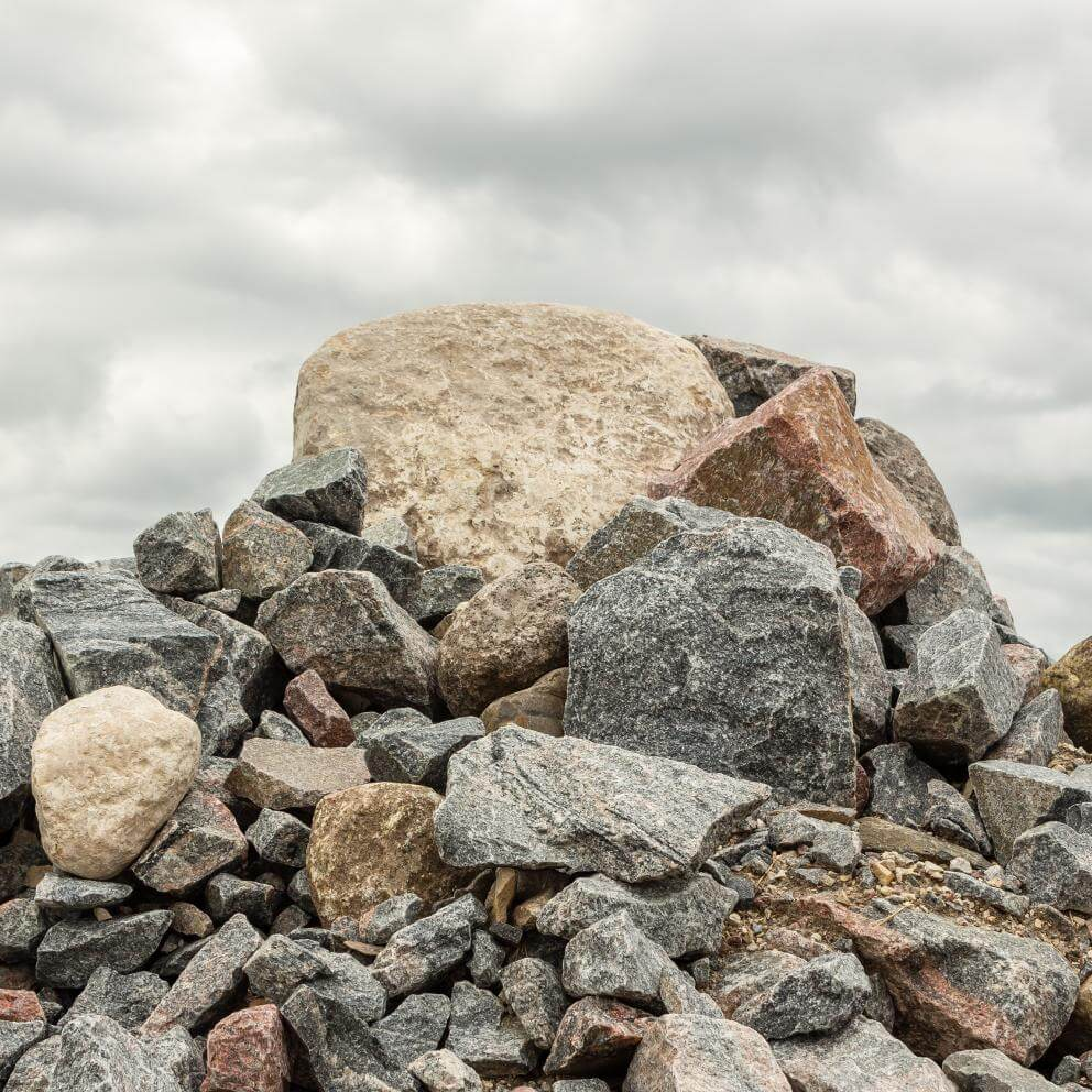 Pile of huge rocks and boulders under dark grey sky - Stock image